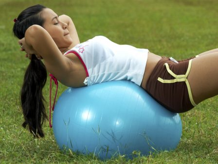 Doing Exercise In The Park Using An Exercise Ball